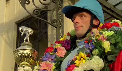 "Vittel Water advertisement: Proud jockey with flowers around his neck holds his racing trophy of a ""man carrying horse"""